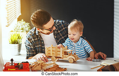 father and son toddler gather craft a car out of wood and...