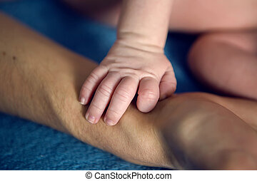 father holds the hand of his baby son