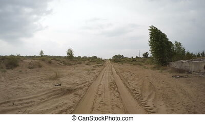 Rear view of car driving along a rural dirt road - A view of...