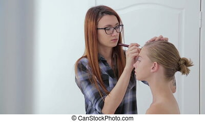Makeup artist applying liquid tonal foundation on girl's...