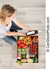 Woman Looking At Grocery Box