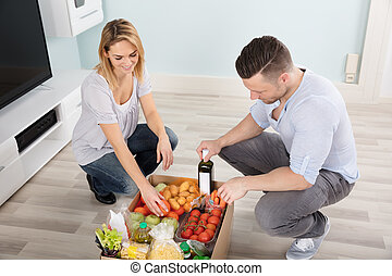 Couple Looking At Groceries In The Cardboard Box
