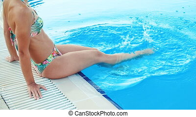 young brunette woman in bikini and sunglasses sitting on...
