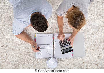 Elevated View Of A Couple Calculating Invoice - Elevated...