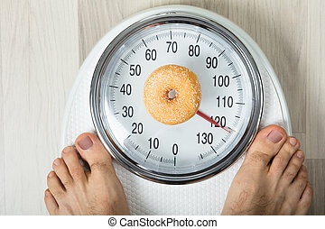 Donut And A Person On Weighing Scale - Close-up Of A Person...
