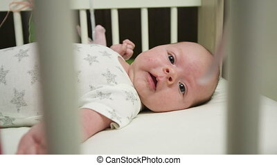 Baby in White Crib - Cute baby playing with feet in baby...