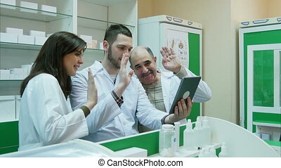Team of pharmacist having video chat using digital tablet at...