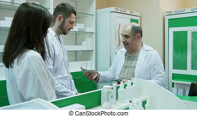 Senior pharmacist giving salary in dollar to his young...