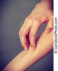 female scratching her itchy arm with allergy rash