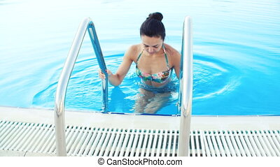 young brunette woman in bikini and sunglasses gets out swimming pool on Sunny summer day