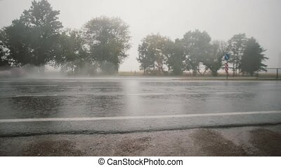 A view of cars passing by on the road in the rain, splashing water around. Trees on the other side.