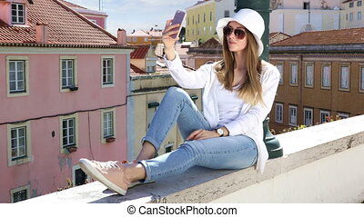 Young pretty girl makes selfie photo and talking on a mobile...