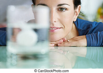 woman looking at aspirin in glass of water - cropped view of...