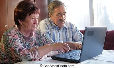 An elderly couple is sitting at home at the laptop. Woman...