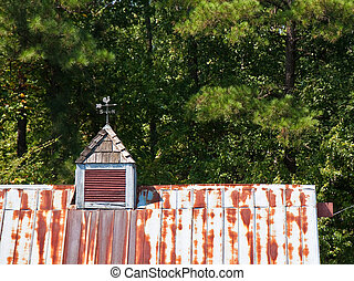 Rusty Tin Roof Cupola and Weathervane - Rusty tin roof of an...