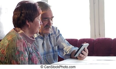 An elderly couple communicates with their grandchild by video linking the tablet. A man and a woman are talking to relatives.
