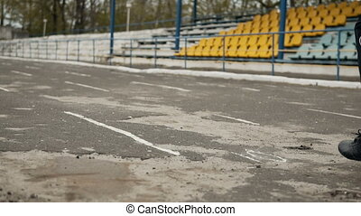 Jogger at the Stadium - Jogger runs on asphalt path of old...