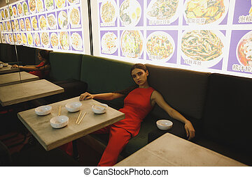 Woman lying on armchair in eatery - Woman in suit lying on...