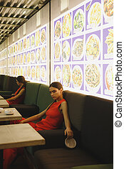 Side view of serious woman lying on armchair in eatery