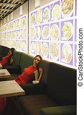 Side view of young woman lying on armchair in eatery - Side...