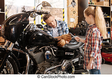 Adorable young girl assisting her dad - Little helper....