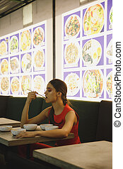 Vertical image of Woman eating in eatery - Vertical image of...