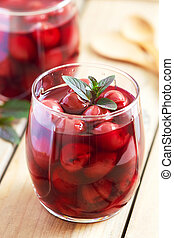 Sour cherry compote dessert served with mint leaves
