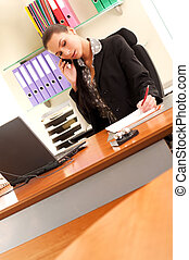 Business woman sitting in the office and making business calls
