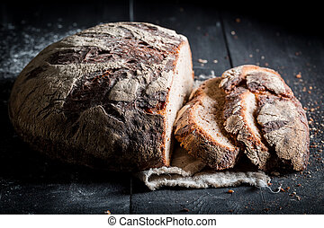 Healthy sliced loaf of bread for breakfast on dark table