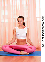 Portrait of pretty young woman doing yoga exercise on mat