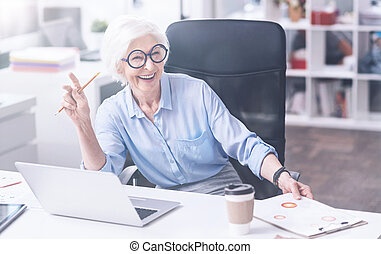 Positive delighted elderly woman sitting on office chair -...