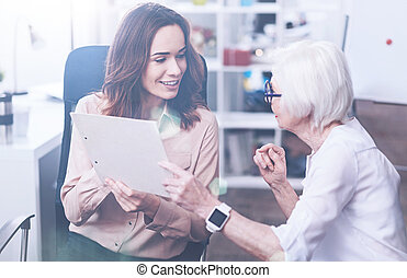 Serious elderly woman giving folder to her coworker - Do not...