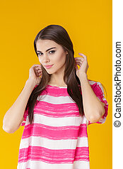 young beautiful smiling woman with long hair in pink shirt on yellow background.
