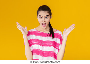portrait of surprised young brunette woman in pink shirt on yellow background. girl looks at camera