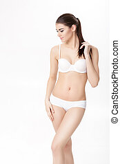 beautiful young brunette woman with perfect sporty body in white lingerie on white background