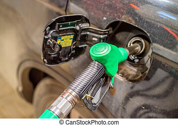 Refilling the car with fuel - Close-up of fuel nozzle...