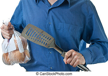 Mid-section of man in holding spatula and burger buns - The...