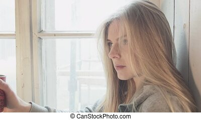 Young happy blonde using smartphone communicates with boyfriend sitting on window. A bright smiling young woman is drinking coffee and writing a message on the phone while sitting on the windowsill.