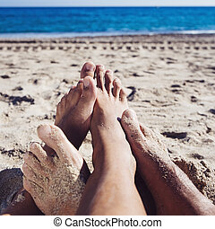 men playing footsie on the beach - closeup of the feet of...