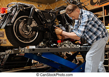 Strong industrious tinker using a wrench - Make it sit...