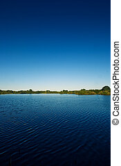 Lake and blue sky - The picture shows a lake and a blue sky.