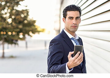Businessman wearing blue suit and tie using a smartphone. -...