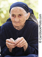 Recollection - Serious elderly woman recollecting while...