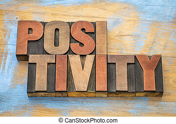 positivity word abstract in wood type
