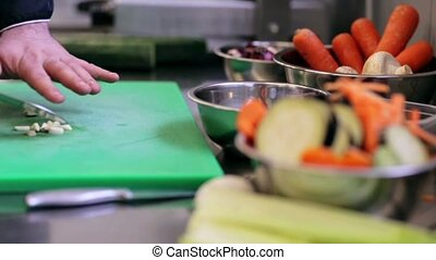 hands of male chef cook chopping garlic in kitchen -...