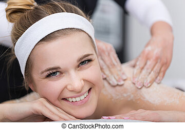 Woman getting exfoliating salt scrub massage at beautician's...