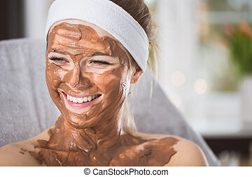 Young woman during refreshing chocolate mask treatment in...