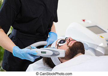 Men's anti-aging laser therapy - Man at beautician's during...
