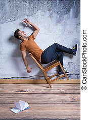 Man falling down from chair - Afraid young man falling down...