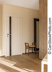 House corridor in neutral colours with white door and chair
